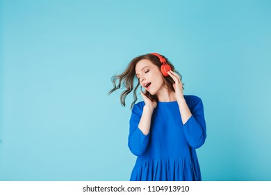 Portrait of young pretty lady in blue dress dancing while listening music in headphones on over pink background