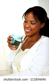 Portrait of a young pretty lady smiling and drinking fresh water while looking to the glass