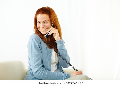 Portrait of a young pretty lady using a phone and smiling while looking at you