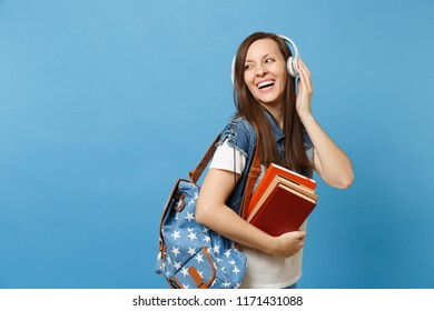 Portrait of young pretty laughing woman student in denim clothes with backpack headphones listening music holding school books isolated on blue background. Education in high school university college