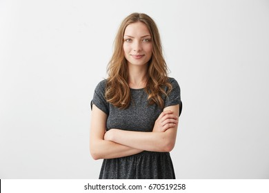 Portrait of young pretty positive girl smiling looking at camera with crossed arms over white background.