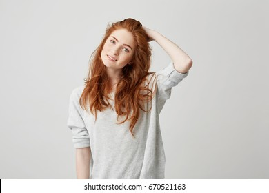 Portrait of young pretty redhead girl with freckles looking at camera smiling touching hair over white background.
