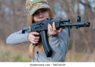 Portrait of Young pretty slim blond girl in a camouflage cap with big black gun aims in someone near forest in cold autumn day close up