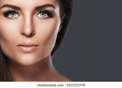 Portrait of young and pretty woman with a artificial eyelashes on dark gray background