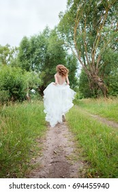 portrait of young pretty woman (bride) in white wedding dress outdoors running away