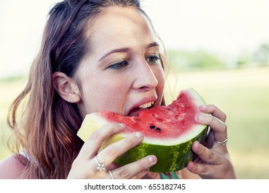 portrait of young pretty woman eating a slice of watermelon outdoors