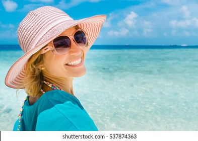 Portrait of young pretty woman with hat on the beach