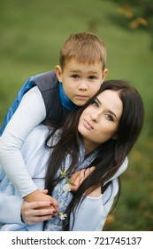 Portrait of a young and pretty woman and her son, a child in autumn clothes hugged Mom, a lady loves her child and treats him with tenderness and attention
