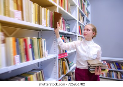 Portrait of a young pretty woman in the library. Young librarian searching books and taking one book from library bookshelf