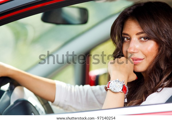 Portrait of young pretty woman in the red car