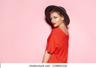 Portrait of young pretty woman with shiny pure skin on pink background. Well-dressed model in trendy autumn clothes.
