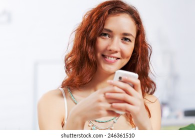 Portrait of young pretty woman sitting at cafe and using mobile phone