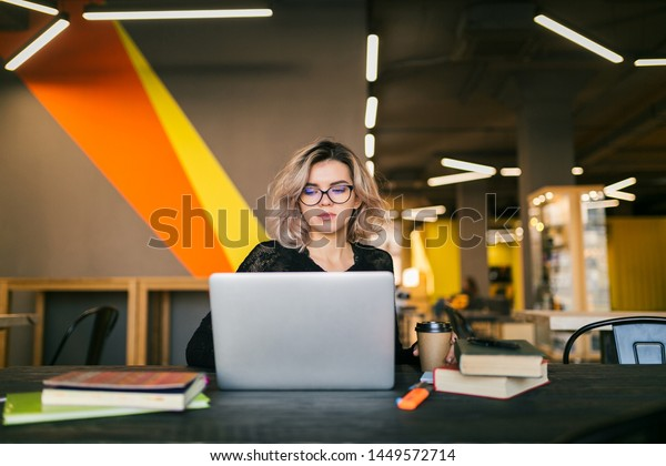 portrait of young pretty woman sitting at table in black shirt working on laptop in co-working office, wearing glasses