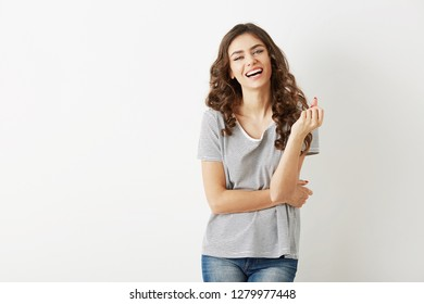 portrait of young pretty woman in t-shirt laughing, isolated, happy, sincere smile, long curly hair, white teeth