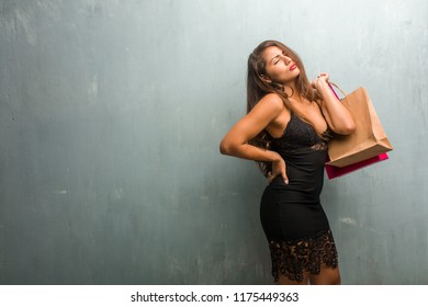 Portrait of young pretty woman wearing a dress against a wall with back pain due to work stress, tired and astute. Holding shopping bags.