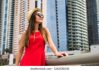 Portrait of young pretty woman wearing in red dress and sunglasses, straw hat in front of skycrapers in modern city