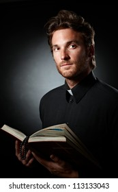 Portrait of young priest with Bible and rosary handheld.