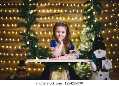 portrait of young princess with snowman at seesaw