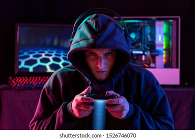 Portrait of the Young  Pro Gamer Playing in Online Video Game. Neon and magenta Colored Room. e-Sport Cyber Games Internet Championship. Motion sweep in image.