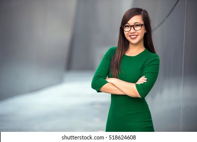Portrait of a young professional business woman staff leader confident with arms folded