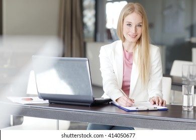 Portrait of young professional businesswoman writing on paper while sitting at office in front of laptop.