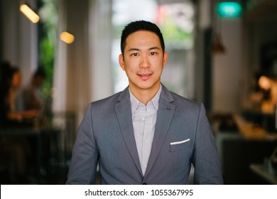 Portrait of a young, professional and handsome Chinese Asian lawyer. He is in a grey suit and white pocket square and is smiling at the camera. He is well groomed and put together and is smiling.