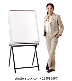 Portrait of a young professional Hispanic business woman standing next to a presentation easel