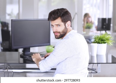 Portrait of young professional sitting at design studio in front of his personal computer. Creative man turning back while looking at camera and smiling.
