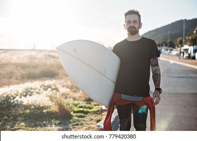 Portrait of young professional surfer man with tattoos and beard, who wears blank black tshirt and holds his surfboard under arm. Light leak from sunset sun behind shoulder. relaxed lifestyle