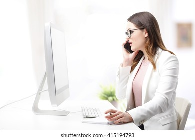 Portrait of young professional woman sitting at desk in front of computer and making call.