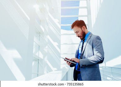 Portrait of young prosperous business man dressed in suit work on digital tablet during break, skilled male entrepreneur dressed in corporate clothes using touch pad while standing in modern office