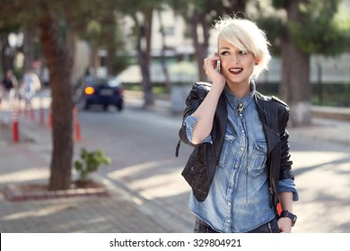 portrait of a young punk style blond woman outdoor, talking with her mobile phone
