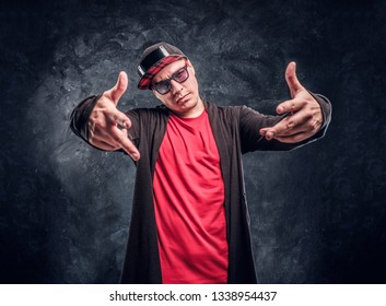 Portrait of a young rapper dressed in a hip-hop style, posing for a camera. Studio photo against a dark textured wall