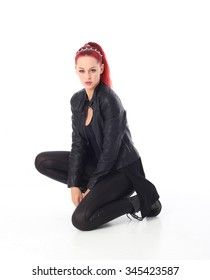 portrait of young red haired fashion model wearing black leather pants and urban jacket posing against white background. kneeling on the ground.