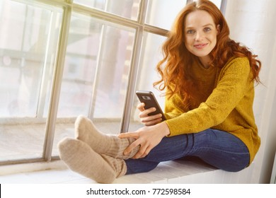 Portrait of young red-haired smiling woman sitting on windowsill with mobile phone - Shutterstock ID 772598584