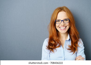 Portrait of young red-haired woman wearing glasses against blue background