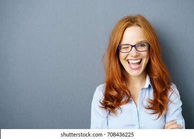 Portrait of young red-haired woman wearing glasses winking against blue background