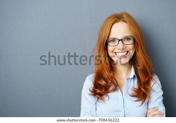 Portrait von jungen Rothaärchenfrauen mit Brille auf blauem Hintergrund