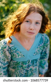 Portrait of young redhead curly blue-eyed girl with freckled skin wearing blue dress looking at camera