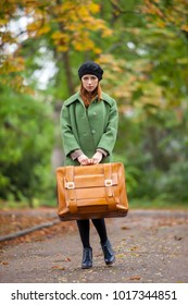 Portrait of young redhead girl in green coat with suitcase at autumn season outdoor