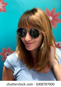 Portrait of a young redhead girl (woman) wearing sunglasses. Rear background blue with flowers.
