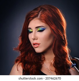 Portrait of a young redhead woman with colorful make up