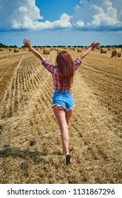 Portrait of young redhead woman in jeans shorts. Cowgirl and haystacks against blue sky with clouds. Summer field with hay.