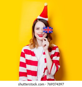 Portrait of young redhead woman in Santa Claus hat and striped shirt with Great Britain flag on yellow background. Christmas time