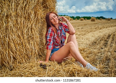 Portrait of young redhead woman speaks on the phone. Jeans shorts. Cowgirl on haystack against blue sky with clouds. Summer field with hay.