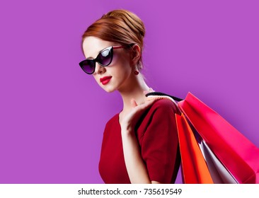 Portrait of young redhead woman in sunglasses with shopping bags on purple background