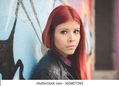 portrait young redhead woman venezuelan looking camera outdoor city pensive - serious, determination, girl power concept