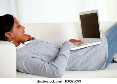 Portrait of a young relaxed woman working on laptop while is lying on sofa at home