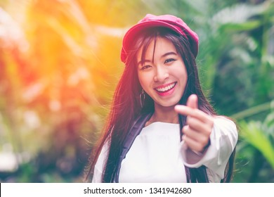 Portrait of young relaxing asian girl feeling freedom raised her hands in the air, Beautiful Smiling carefree Woman in the nature park with happy emotion. woman lifestyle, People freedom style.