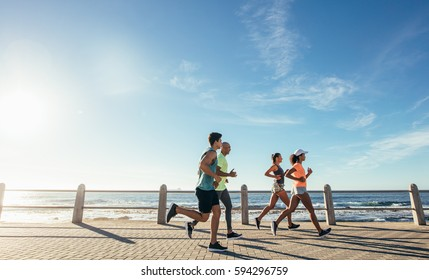 Portrait of young runners on the sea front path along the shoreline. Group running along a seaside promenade.